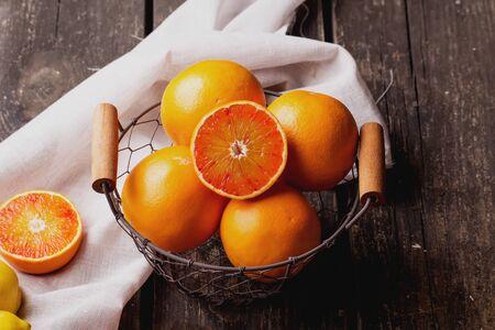 Bio bloody oranges and lemons in the basket on rustic wooden board, cut in halves. Top View 写真素材