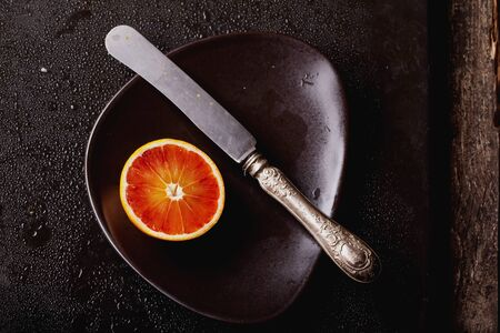 Bio bloody oranges cut in half on a plate with knife on marble board. Top View