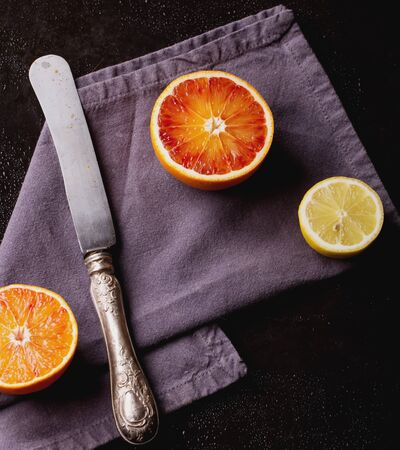 Bio bloody oranges and lemon cut in half with napkin and knife on black metal board. Top View