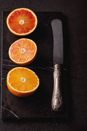 Bio bloody oranges cut in half with knife on marble board. Top View