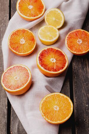 Bio bloody oranges and lemon with napkin on rustic wooden board, cut in halves. Top View 写真素材