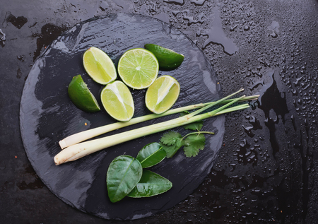 lemongrass tea: Limes, lime leaves, lemongrass as ingeridents for cold lemonade or iced tea or thai cuisive with olive tree citrus juice squeezer Stock Photo