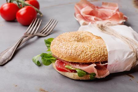 hams: Bagels con prosciutto de jamón italiano, queso crema, tomates y ensalada envueltos en papel sobre fondo de metal rústico