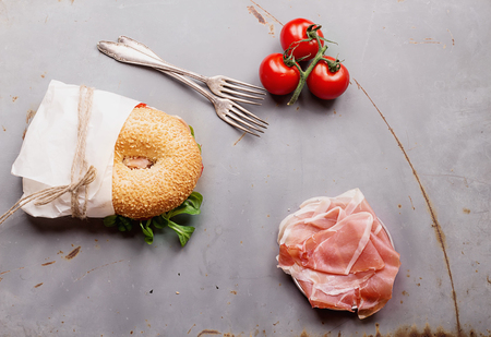 Bagels with Italian ham prosciutto, cream cheese, tomatoes and salad wrapped in paper on rustic metal background. Top View