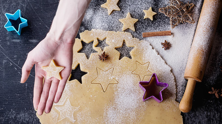Christmas star cookies preparation. A piece of sweet vanilla dough rolled over the black background and male hand cutting the cookies with a star form. Top View