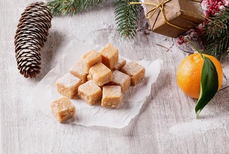 Creamy Caramel fudge on grey background with furt tree and christmas decoration Stock Photo