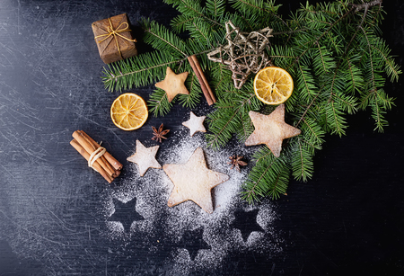 fur tree: Freshly cooked Christmas star cookies over a black background with sugar powder and different christmas decration, fur tree and spices
