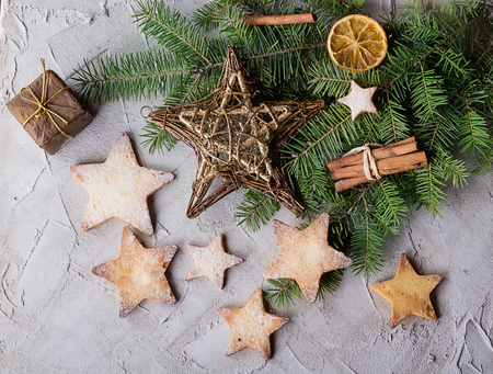 fur tree: Freshly cooked Christmas star cookies over a grey background with sugar powder and different christmas decration, fur tree and spices