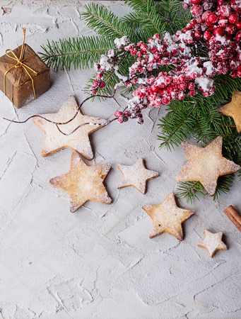 freshly cooked christmas star cookies over a grey background with sugar powder and different christmas decration