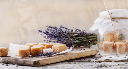 Caramelos caseros cremosos con sabor a lavanda, servidos en la tabla de madera vintage con cubos de azúcar y flores de lavanda