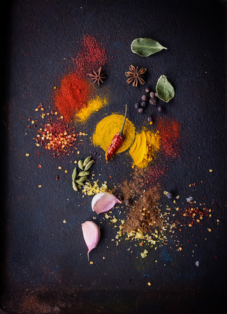 tumeric: Herbs and spices selection (turmeric, paprika, lime leaf, juniper berries, salt, pepper, oregano, garlic, chili) on dark rustic background. Top View Stock Photo