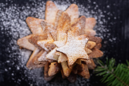 fur tree: Freshly cooked Christmas star cookies  served in a pyramid over a black background with sugar powder and different christmas decration, fur tree and spices