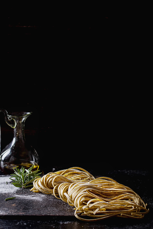 Raw uncooked black pepper spaghetti pasta with flour, egg rosemary, salt and spices and olive oil on vintage metal board over dark background. Space for text. Stock Photo