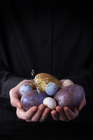 Male hands holding Chocolate Easter Eggs. Rustic Easter Concept. Copy Space