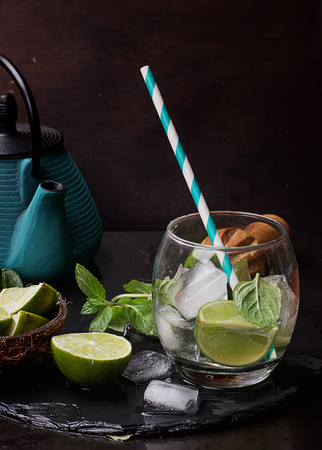 lemongrass tea: LimeIce tea  with  chinese tea pot mint, lime leaves and ice served in glasses on slate board. Dark Rustic Style Stock Photo