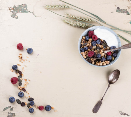 Granola brunch with blueberries and raspberries on rustic wooden table with wheat spiklets. Top View