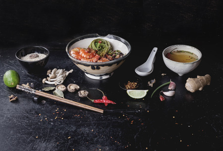 Green tea soba noodles  served with shrimps,  shiitake mushrooms and spicy broth.  Decorated with different spices and condiments used during preparation: garlic, lime, chili pepper, shimeji mushrooms