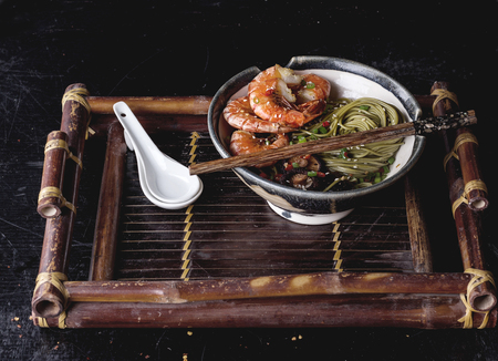 Green tea soba noodles  served with shrimps,  shiitake mushrooms and spicy broth on a vintage bamboo tray.