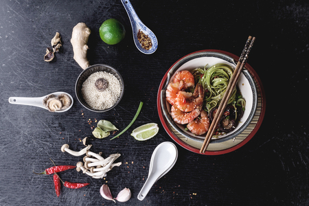 Green tea soba noodles  served with shrimps,  shiitake mushrooms and spicy broth on round traditional tray.  Decorated with different spices used during preparation: garlic, lime, chili pepper, shimej