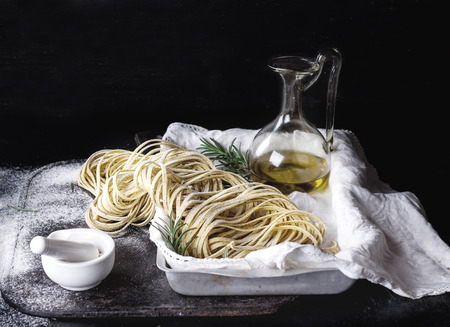 Raw uncooked black pepper spaghetti pasta with flour, egg rosemary, salt and spices and olive oil on vintage metal tray over dark background. Space for text