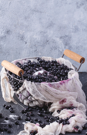 Wild blueberries in metal basket served with sugar on rustic stone board decorated with napkin. Copy space