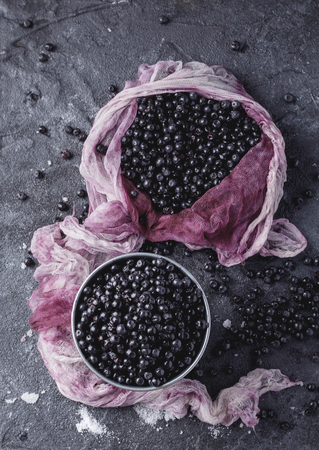 Wild blueberries in textile napkin served with sugar on rustic stone board decorated. Top View 写真素材