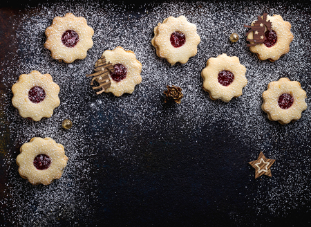 Home Made Cristmas cookies on the rustic black wooden background, decorated with Christmas toys. Top View