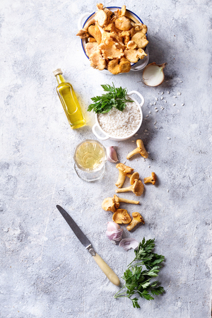 Ingredients for mushroom Risotto: chanterelle mushrooms, arborio rice, garlic, wine, onion parsley and olive oil over a stone board. Top View. Copy space.