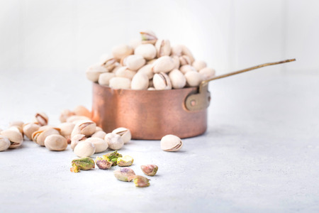 Freshly roasted pistachios  in a copper pan over a stone background