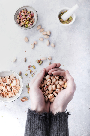 Freshly roasted pistachios in the male hands over a stone background. Top View. Copy Space 写真素材