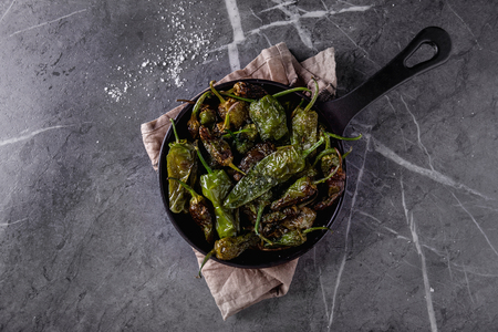 Traditional Spanish Tapas Pimientos de Padron - fried small peppers serves with sea salt. Top View. Copy Space