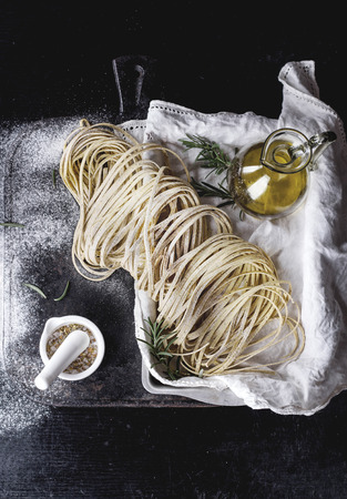 Raw uncooked black pepper spaghetti pasta with flour, egg rosemary, salt and spices and olive oil on vintage metal tray over dark background. Top view with space for text.