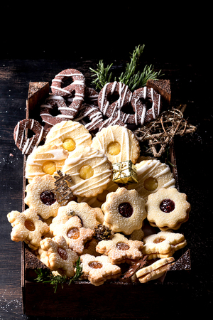 Home Made  set of Cristmas cookies on the rustic black wooden background, decorated with Christmas toys and fir tree.