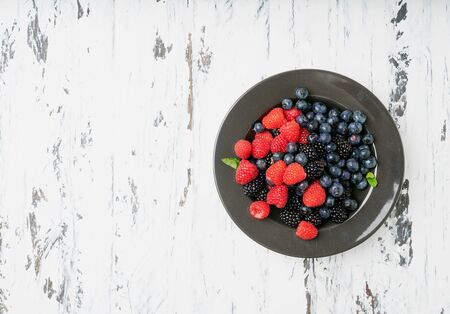 Ripe and juicy fresh berries in the bowl over white rustic wooden backgrounds. Blueberry, Raspberry and Blackberry. Top view