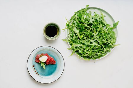 Marbled beef carpaccio decorated  with arugula leaf, parmesan cheese and sliced hard-boiled egg over the plate. Fresh arugula salat on the plate. Bowl of balsamic vinegar. White background. Top view. Banque d'images