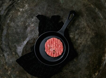 Raw Ground beef meat Burger steak cutlet with seasonings served on metal frying pan over the kitchen towel. Rustic metal background. Top view