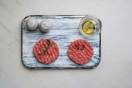 Raw Ground beef meat Burger steak cutlets with seasonings and rosemary served on rustic wooden board with salt and pepper shakers and glass of olive oil. White marble background. Top view