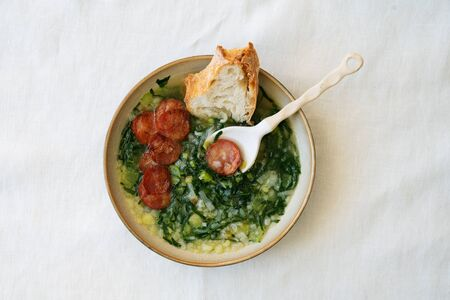 Caldo Verde Soup with greens and chopped chorizo on the top in ceramic bowl with ceramic spoon and piece of bread. Top View