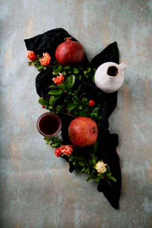 Pomegranate juice in the glass and in the jug with pomegranate fruits on the napkin decorated with pomegranate flowering branches over rustic background. Top view. Standard-Bild