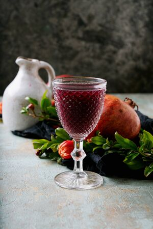 Pomegranate juice in the glass and in the jug with pomegranate fruits on the napkin decorated with pomegranate flowering branches over rustic background. Side view. Selective focus