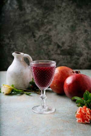 Pomegranate juice in the glass and in the jug with pomegranate fruits decorated with pomegranate flowering branches over rustic background. Side view. Selective focus Standard-Bild