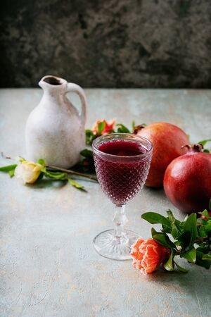 Pomegranate juice in the glass and in the jug with pomegranate fruits decorated with pomegranate flowering branches over rustic background.Selective focus