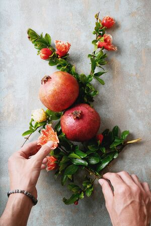 Male hands decorating pomegranate fruits with pomegranate flowering branches over rustic background. Top view