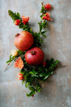 Pomegranate fruits decorated with pomegranate flowering branches over rustic background. Top view Standard-Bild