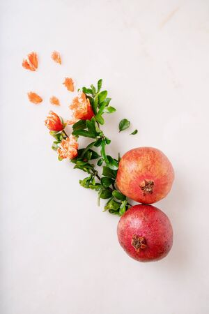 Pomegranate fruits decorated with pomegranate flowering branches and petals over white marble background. Top view