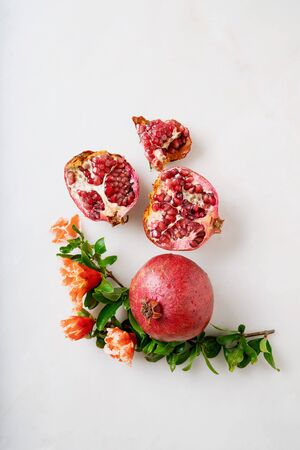 Pomegranate fruits, whole and halfs, decorated with pomegranate flowering branches over white marble background. Top view