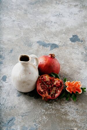 Pomegranate fruits, whole and half, jug of pomegranate juice, decorated with pomegranate flowering branch over rustic background. Selective focus