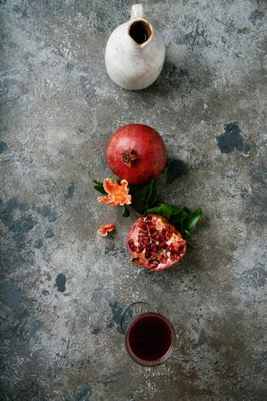 Jug of pomegranate juice, pomegranate fruits, whole and half, decorated with pomegranate flowering branch, glass of pomegranate juice over rustic background. Top view