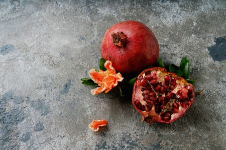 Pomegranate fruits, whole and half, decorated with pomegranate flowering branch over rustic background. Top view. Close up. Copy space Banque d'images
