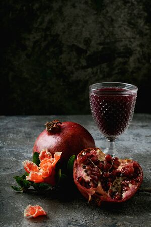 Pomegranate fruits, whole and half, Glass of pomegranate juice, decorated with pomegranate flowering branch over dark rustic background. Side view. Close up. Selective focus